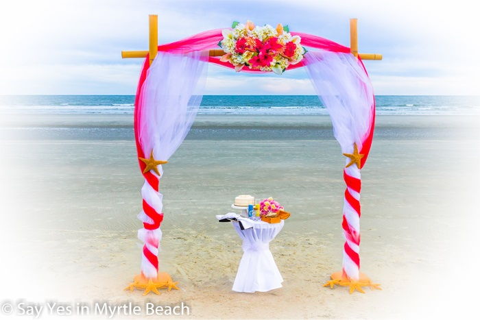 Red and white tulle wrapped arbor