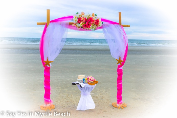Magenta and white tulle wrapped arbor
